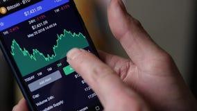 Equipaggi l'uso uno smartphone per Internet che vende la valuta cripto Movimento lento stock footage