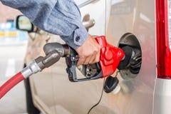 Equipaggi la benzina di pompaggio della mano con l'insetto sulle luci dell'automobile immagine stock libera da diritti