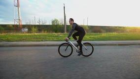 Equipaggi la bici fissa di guida dell'ingranaggio sulla strada al tramonto stock footage