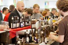 Equipaggi la birra d'acquisto al contatore della barra in folla della gente Fotografia Stock