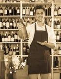 Equipaggi la bottiglia della tenuta del venditore di vino in negozio Immagini Stock Libere da Diritti