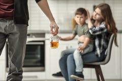 Equipaggi la bottiglia della tenuta dell'alcool mentre moglie che abbraccia il loro figlio fotografia stock
