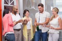 Equipaggi la bottiglia schioccante di champagne con il suo gruppo fotografia stock