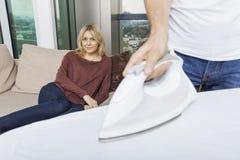 Equipaggi la camicia rivestente di ferro mentre donna che si rilassa sul sofà a casa Immagini Stock Libere da Diritti