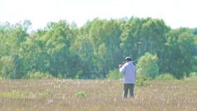 Equipaggi la camminata intorno con un bastone del golf sulla sua spalla sul campo dell'estate stock footage