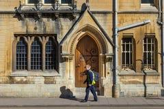 Equipaggi la camminata sul marciapiede davanti ad una vecchia costruzione dell'ONU di Oxford Fotografia Stock