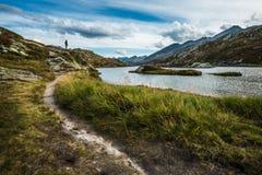 Equipaggi la camminata in una traccia di montagne nelle alpi della Svizzera con il lago immagini stock