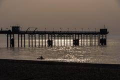 Equipaggi la canoa sul mare e sulle siluette del pilastro all'ora dorata Fotografia Stock Libera da Diritti