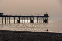 Equipaggi la canoa sul mare e sulle siluette del pilastro all'ora dorata Fotografie Stock