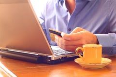 Equipaggi la carta di credito della tenuta della mano accanto al computer portatile ed alla tazza di caffè Concetto online di acq Fotografie Stock