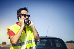 Equipaggi la chiamata alla società di assicurazioni dopo una ripartizione dell'automobile Fotografia Stock