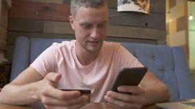 Equipaggi la compera online facendo uso della carta di credito e dello smartphone stock footage