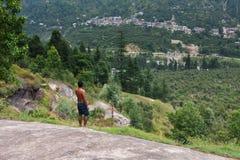 Equipaggi la condizione ad una roccia in foresta verde immagine stock