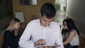 Equipaggi la condizione con il computer portatile ed i suoi colleghi su fondo video d archivio