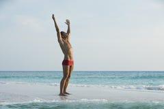 Equipaggi la condizione con il suo braccio outstretched sulla spiaggia Fotografie Stock Libere da Diritti