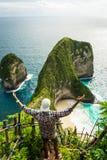 Equipaggi la condizione con le mani sollevate sulla scogliera della spiaggia di Kelingking sull'isola di Nusa Penida Fotografie Stock