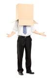 Equipaggi la condizione e gesturing con una scatola di cartone sulla sua testa Fotografia Stock Libera da Diritti