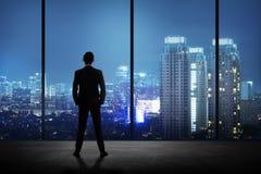 Equipaggi la condizione nel suo ufficio che esamina la città la notte Immagini Stock Libere da Diritti