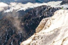 Equipaggi la condizione su un'alta scogliera, sopra le nuvole Fotografie Stock