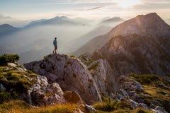 Equipaggi la condizione su una sommità della montagna al tramonto Fotografie Stock