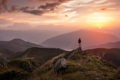Equipaggi la condizione su una sommità della montagna al tramonto Immagini Stock