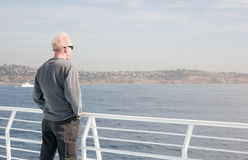 Equipaggi la condizione sulla barca che guarda fuori per innaffiare immagini stock libere da diritti