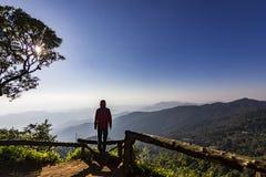 Equipaggi la condizione sulla roccia al tramonto con le montagne qui sotto immagine stock libera da diritti