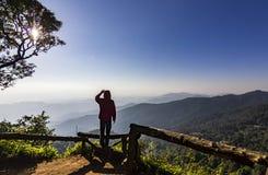 Equipaggi la condizione sulla roccia al tramonto con le montagne qui sotto immagine stock