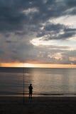 Equipaggi la condizione sulla spiaggia sopra il bello fondo del cielo del tramonto e del mare Fotografie Stock