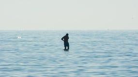 Equipaggi la contemplazione circondata dall'acqua, siluetta di un uomo in mezzo al mare Fotografie Stock