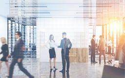 Equipaggi la conversazione con collega in un ufficio occupato Immagine Stock