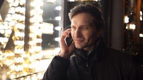 Equipaggi la conversazione sul cellulare sulla via urbana nella sera che sta la stanza frontale di negozio vicina video d archivio