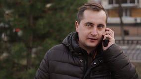 Equipaggi la conversazione sul telefono all'aperto in autunno archivi video