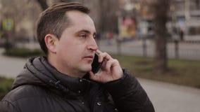 Equipaggi la conversazione sul telefono cellulare mobile facendo uso dello smartphone all'aperto stock footage