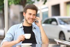 Equipaggi la conversazione sul telefono cellulare in una caffetteria Fotografia Stock