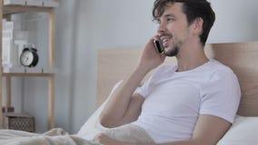 Equipaggi la conversazione sul telefono mentre si trovano dal lato a letto archivi video
