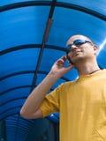 Equipaggi la conversazione sul telefono, sul colore giallo e sull'azzurro Fotografia Stock