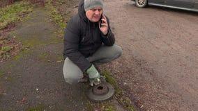 Equipaggi la conversazione sul telefono vicino al disco del freno dell'automobile video d archivio