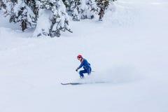 Equipaggi la corsa con gli sci dello sciatore sulla neve bianca fresca sul pendio dello sci Immagine Stock