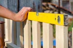Equipaggi la costruzione del recinto di legno ed il controllo con il livello di spirito Chiuda su della sua mano e dello strument Fotografie Stock Libere da Diritti
