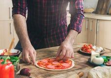 Equipaggi la cottura della pizza in cucina domestica sulla tavola di legno Fotografia Stock