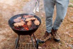 Equipaggi la cottura, solo le mani, lui sta grigliando la carne o la bistecca per un piatto Carne arrostita deliziosa sulla grigl fotografie stock
