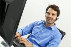 Equipaggi la cuffia avricolare d'uso che dà la chiacchierata online e sostenga Immagine Stock Libera da Diritti