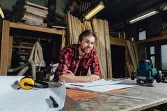Equipaggi la fabbricazione del piano del progetto facendo uso della matita sulla tavola con l'officina su fondo fotografia stock