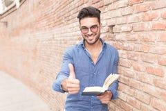Equipaggi la fabbricazione del segno giusto mentre leggono un libro immagine stock