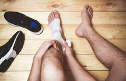 Equipaggi la fasciatura della gamba che si siede sul pavimento di legno Fotografie Stock