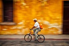 Equipaggi la guida della bici con un fondo variopinto confuso Fotografie Stock Libere da Diritti