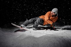 Equipaggi la guida sullo snowboard nella località di soggiorno di montagna nella notte immagine stock libera da diritti