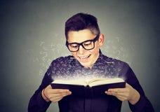 Equipaggi la lettura del libro con le lettere dell'alfabeto che escono Fotografia Stock