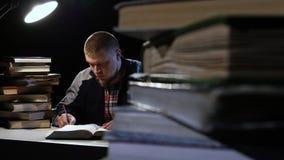 Equipaggi la lettura del libro e scrive in un taccuino Priorità bassa nera video d archivio